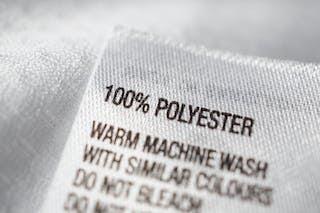 Una etiqueta de ropa que diga 100% poliéster.