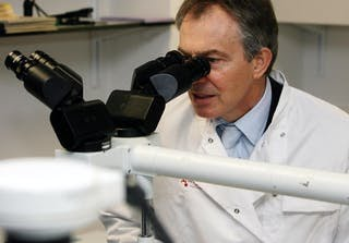 Tony Blair in a lab coat looking through a microscope.