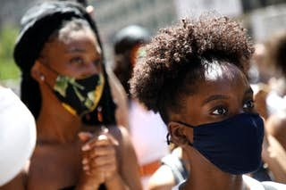 Black woman in a crowd wearing a mask and looking alert